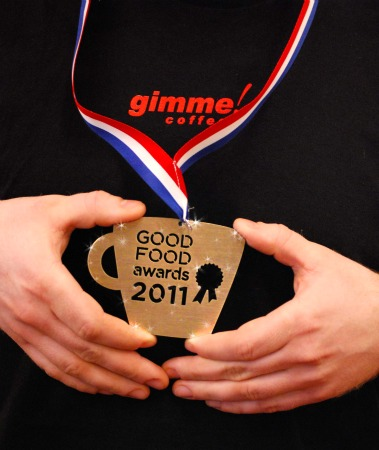 Two hands display a Good Food Awards Medal worn over a Gimme tshirt