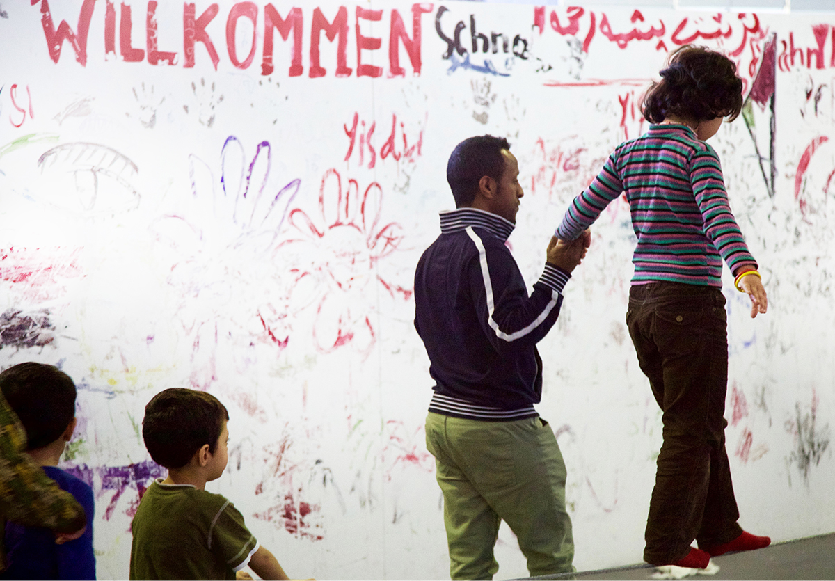 "Father holds his daughter's hand to steady her as she walks on the edge of a wall. In the background, graffiti says ""Wilkommen"""